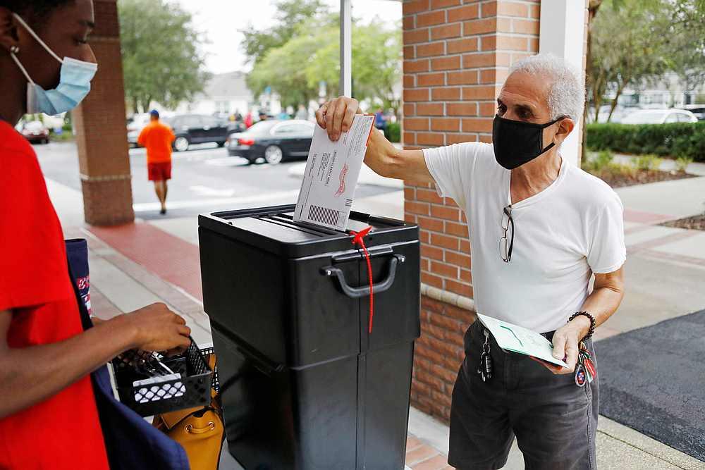 在佛罗里达州奥兰多一个投票站,提前投票的选民将选票放进票箱。-路透社-