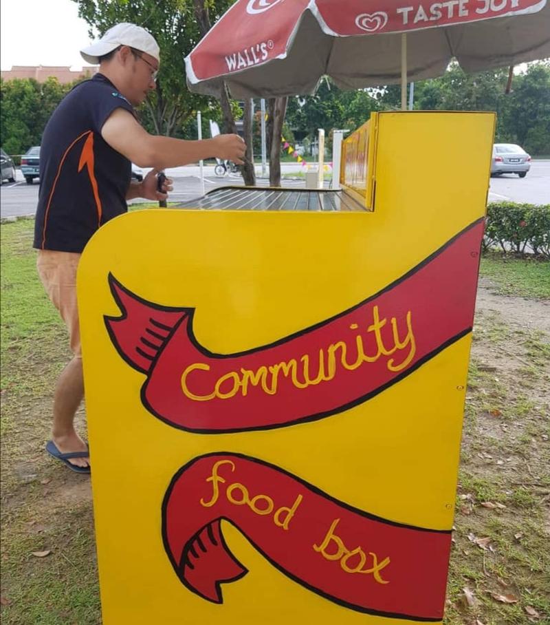 """志工Yap Chin Fei正在帮食物箱""""上色""""。-Alfred Samuel Mariyaras提供-"""