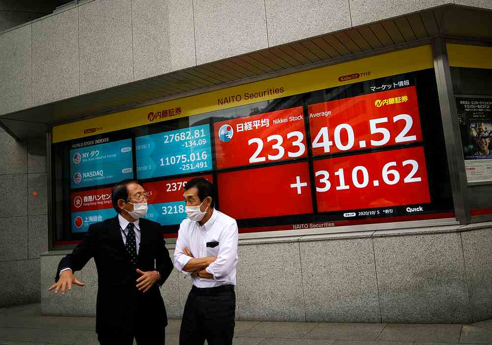 Men wearing protective face masks chat in front of a screen displaying Nikkei share average and world stock indexes outside a brokerage, amid the Covid-19 outbreak in Tokyo Octboer 5, 2020. — Reuters pic