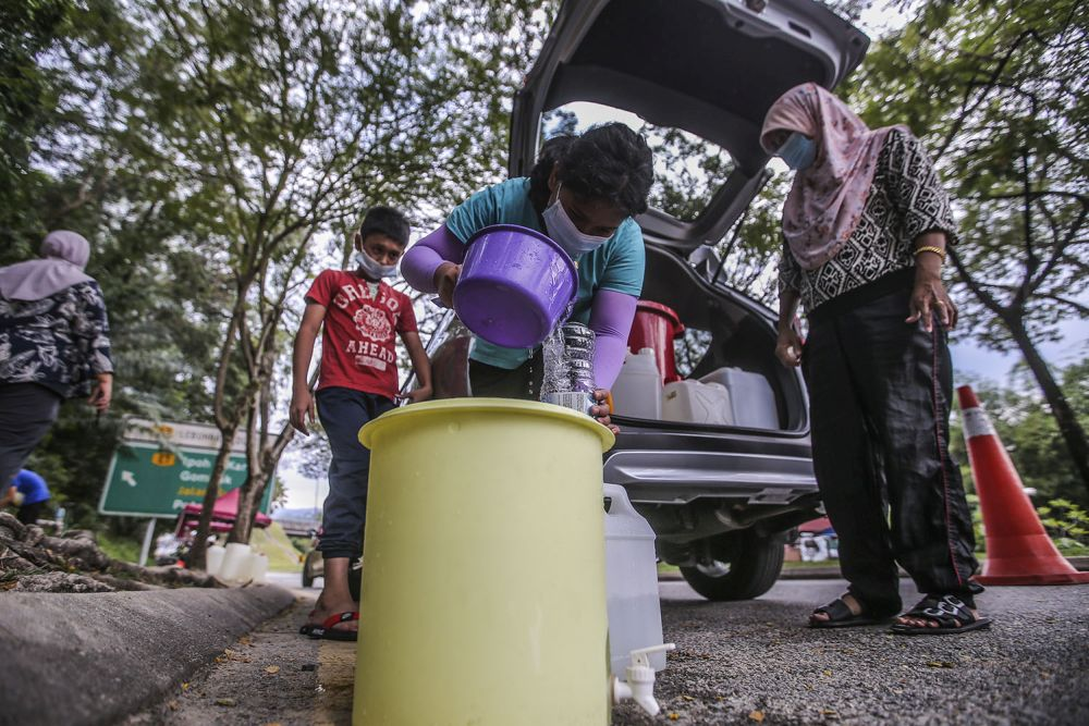 Residents fill their pails at a water point in Keramat AU2 following the latest water disruption October 20, 2020. — Picture by Hari Anggara