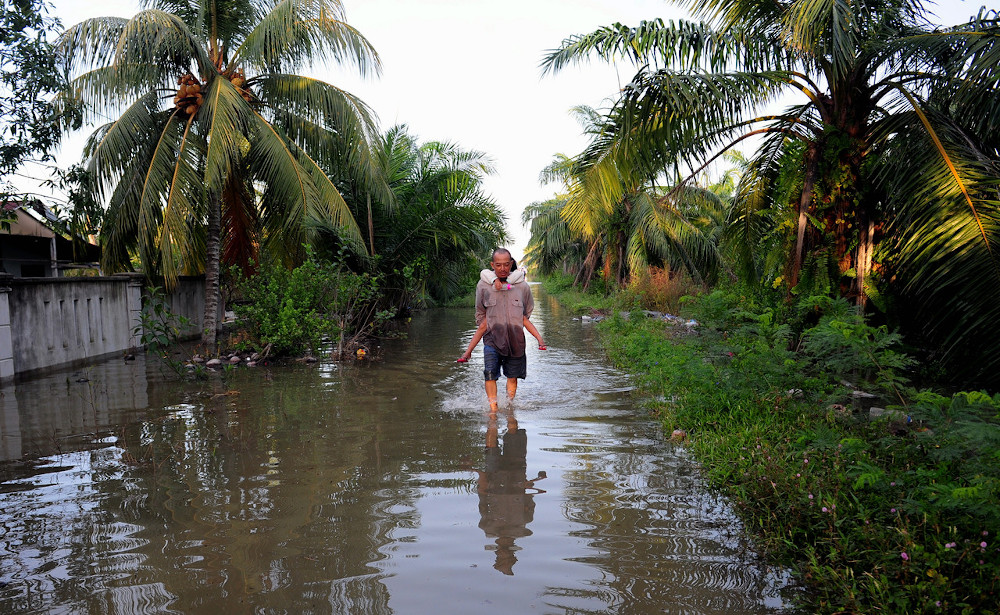 Mohd Hilmi Husi, 48 carries his son, Nia Azzad Mohd Helmi, 5, to leave his house area after it was flooded due to the high tide phenomenon in Kampung Sungai Janggut in Kuala Selangor in this file picture taken on October 18, 2020. — Bernama pic