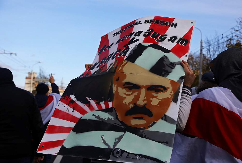 A demonstrator carries a placard depicting Belarusian President Alexander Lukashenko during an opposition rally to reject the presidential election results in Minsk, Belarus October 18, 2020. — Reuters pic