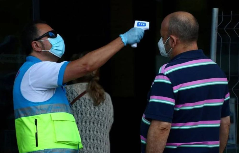 A man gets his temperature checked before a coronavirus disease (Covid-19) antigen test in the working class neighbourhood of Vallecas, which has been under partial lockdown, at a cultural centre in Madrid September 29, 2020. — Reuters pic