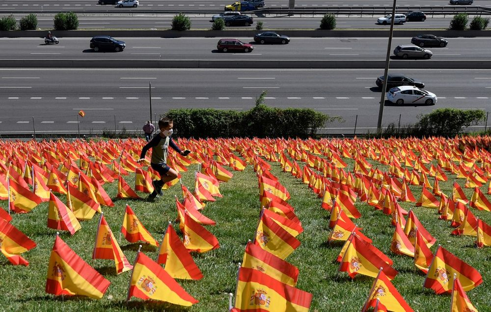 A boy runs among thousands of Spanish flags, representing the Spanish victims of Covid-19, in the Roma park in Madrid, on September 27, 2020. — AFP pic