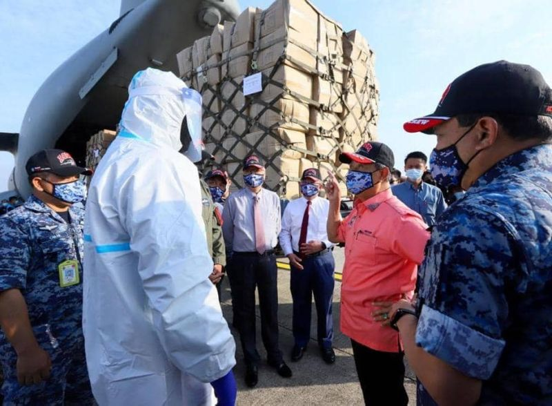 Prime Minister Tan Sri Muhyiddin Yassin speaks to a member of the Malaysian Air Force while inspecting supplies for Sabah and Sarawak at the Subang Air Base October 30, 2020. ― Picture via Facebook