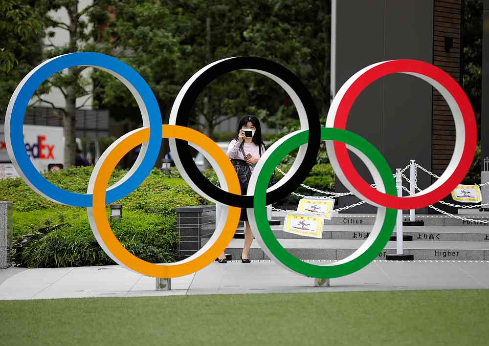 A woman wearing a protective mask amid the Covid-19 outbreak, takes a picture of the Olympic rings in front of the National Stadium in Tokyo, Japan October 14, 2020. — Reuters pic