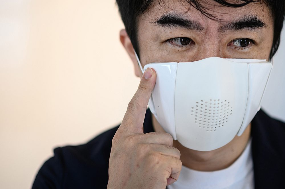 Donut Robotics chief executive Taisuke Ono posing for a photo with the smart mask 'C-face' in his studio. — AFP pic