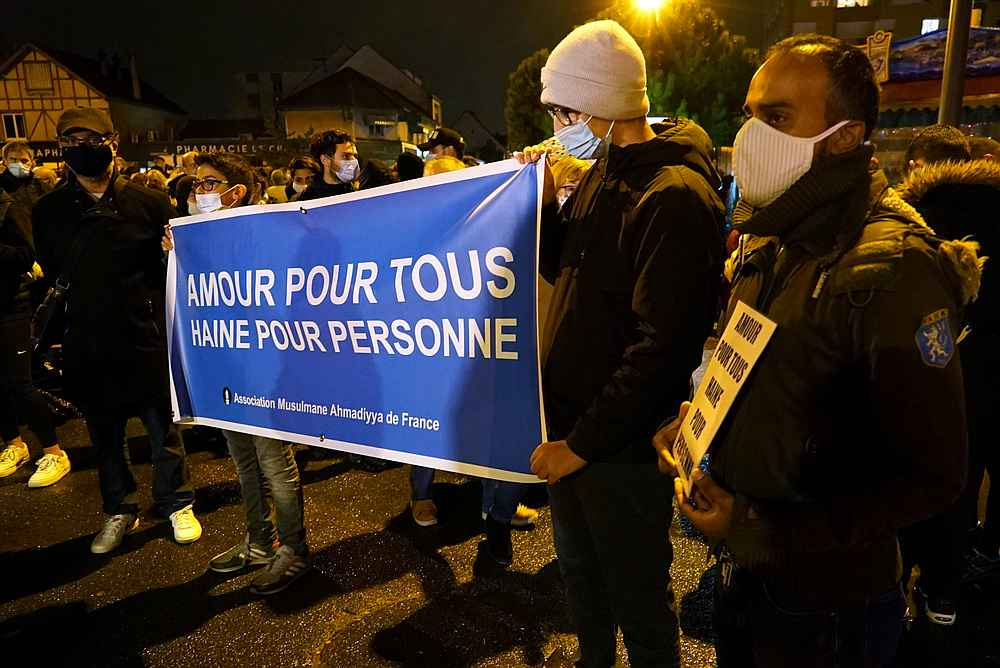 People attend a silent march to pay tribute to Samuel Paty, the French teacher who was beheaded at the Paris suburb of Conflans-Sainte-Honorine, France, October 20, 2020. The slogan reads 'Love for all, hatred for no-one.' — Reuters pic