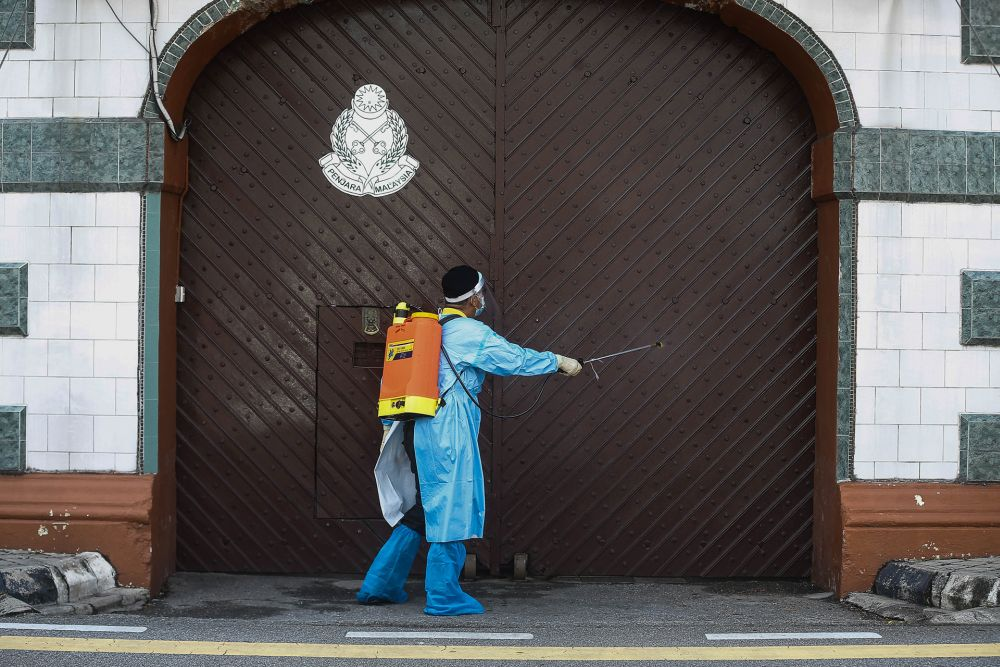 A Penang Remand Prison staff is seen disinfecting the main entrance October 14, 2020. Without revealing the officer's gender and age, Penang Prisons director Roslan Mohamed said the patient was among 26 positive cases reported in the Jawi Prison Cluster yesterday and currently receiving treatment at Penang Hospital. — Picture by Sayuti Zainudin
