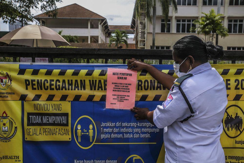 A security guard attaches a notice of closure to the gate of Sekolah Menengah Kebangsaan Bandar Utama Damansara 4 in Petaling Jaya October 12, 2020. — Picture by Hari Anggara