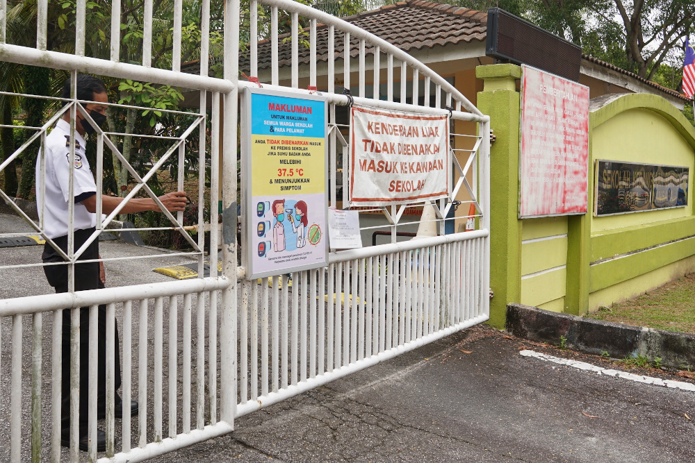 A security guard closes the main gate of a school in Seksyen 11 Petaling Jaya after the Ministry of Education orders to close all school in Selangor for two weeks October 12, 2020. — Picture by Ahmad Zamzahuri