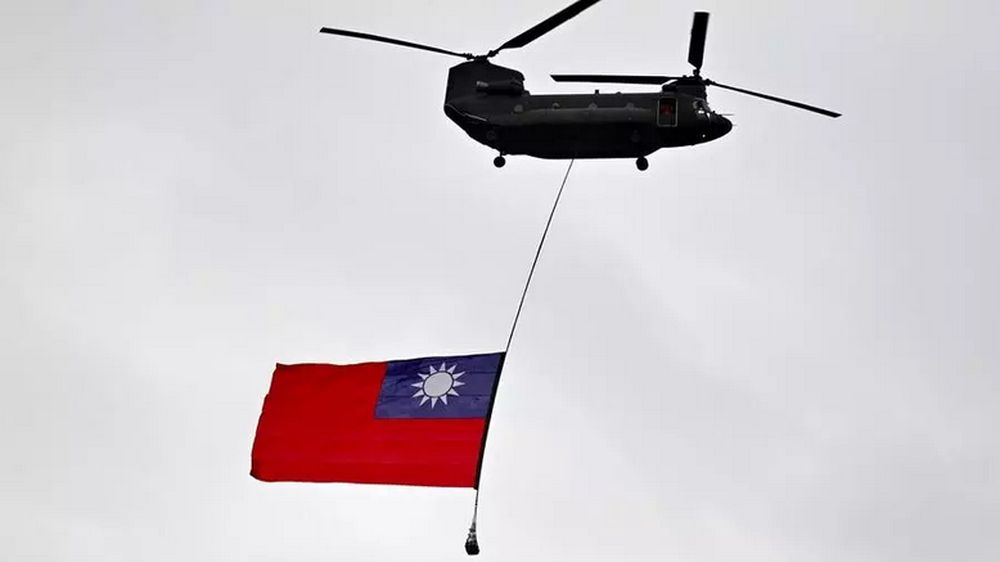 A military helicopter flies a Taiwan flag during a national day parade in Taipei on October 10. Beijing regards Taiwan as its own territory and has vowed to one day seize the self-ruled island. — AFP file pic