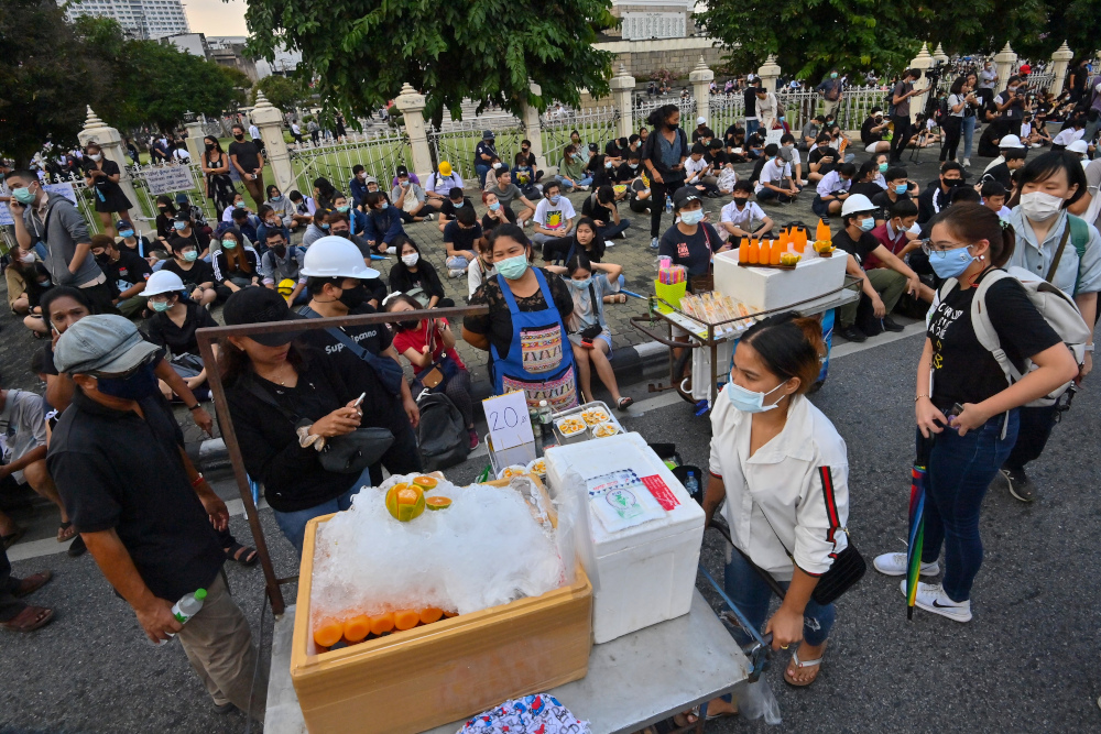 This picture taken October 21, 2020 shows street food vendors selling sandwiches and orange juice setting up stalls during an anti-government rally by pro-democracy protesters in Bangkok. — AFP pic
