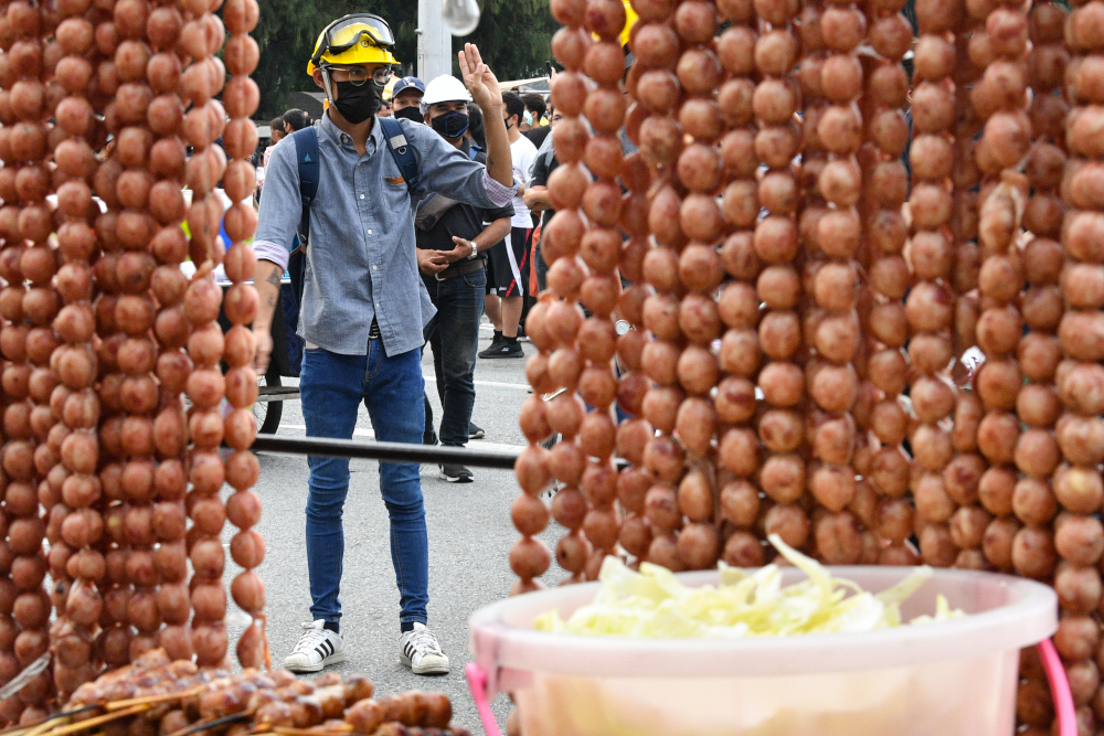 In this file photo taken October 21, 2020, a pro-democracy protesters gestures near a street food vendor selling grilled sausages during an anti-government rally in Bangkok. — AFP pic