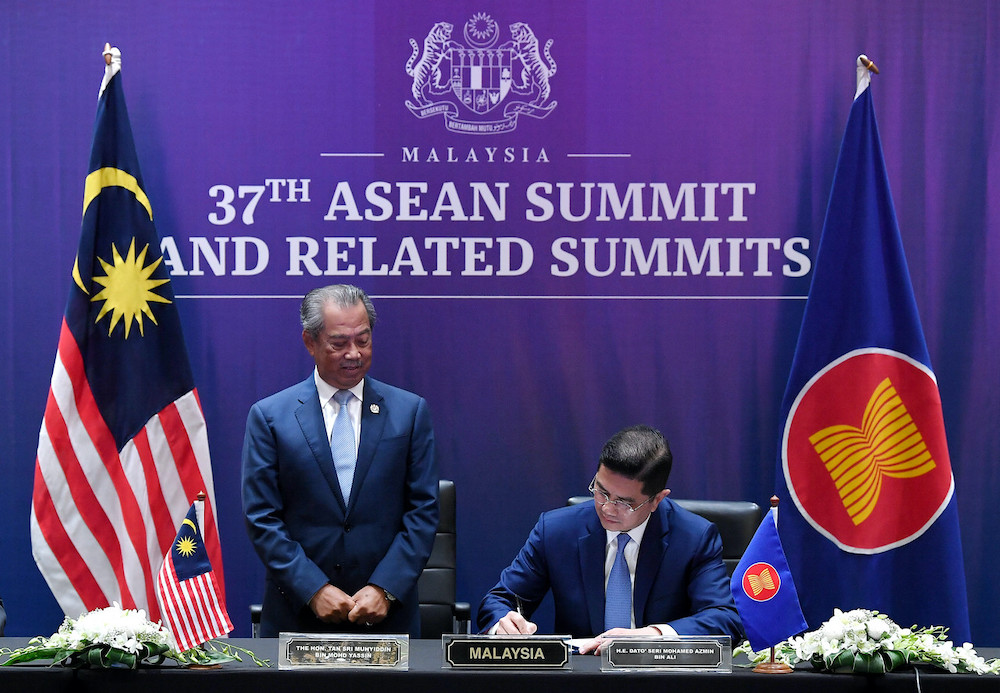 在首相慕尤丁(左)见证下,阿兹敏代表大马政府签署RCEP协定。-马新社-