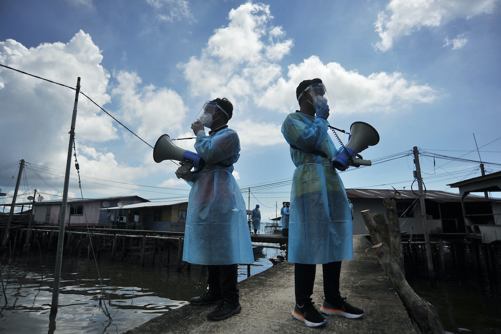 Labuan Health Department personnel on a walkabout at Kampung Bebuloh Laut to increase villagers' awareness of the Covid-19 pandemic, November 12, 2020. — Bernama pic