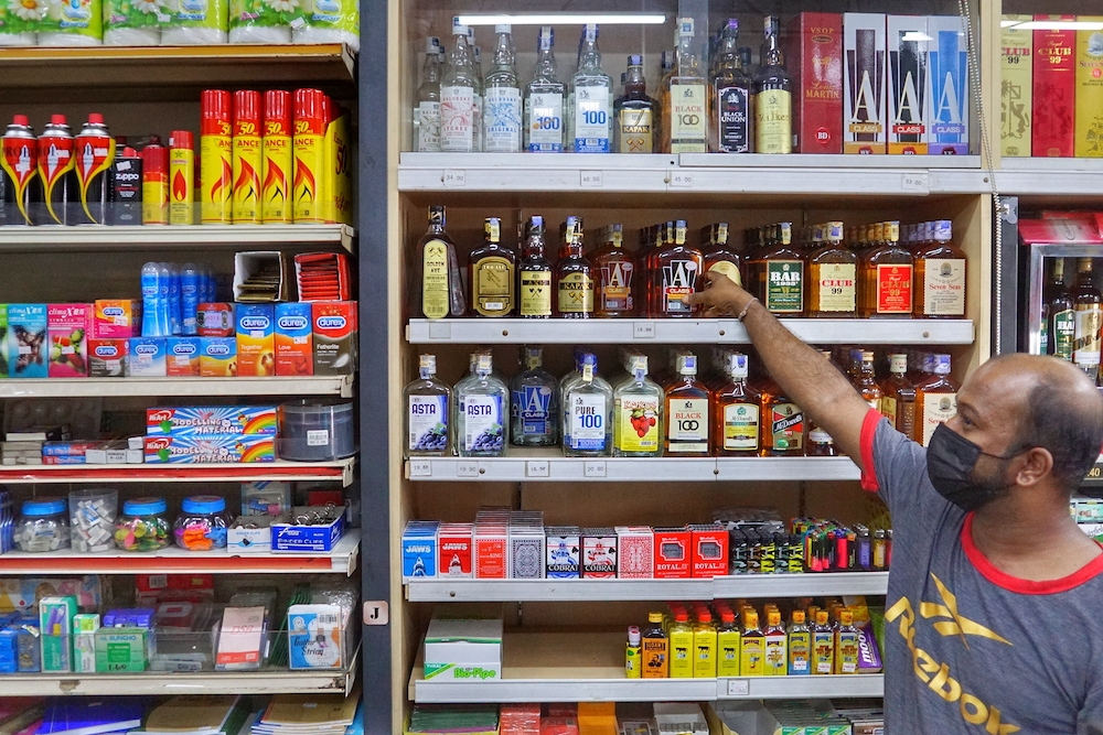 An employee stands in front of liquor bottles in a convenience shop near Sentul November 19, 2020. — Picture by Ahmad Zamzahuri