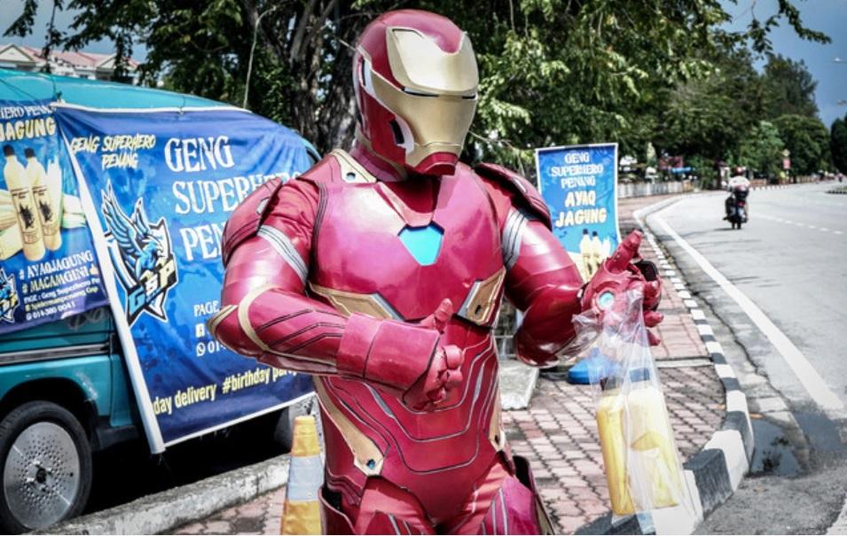 苏古尔为了档口生意,穿着厚重的钢铁侠道具服日晒雨淋的在路边叫卖玉米汁。-马新社-