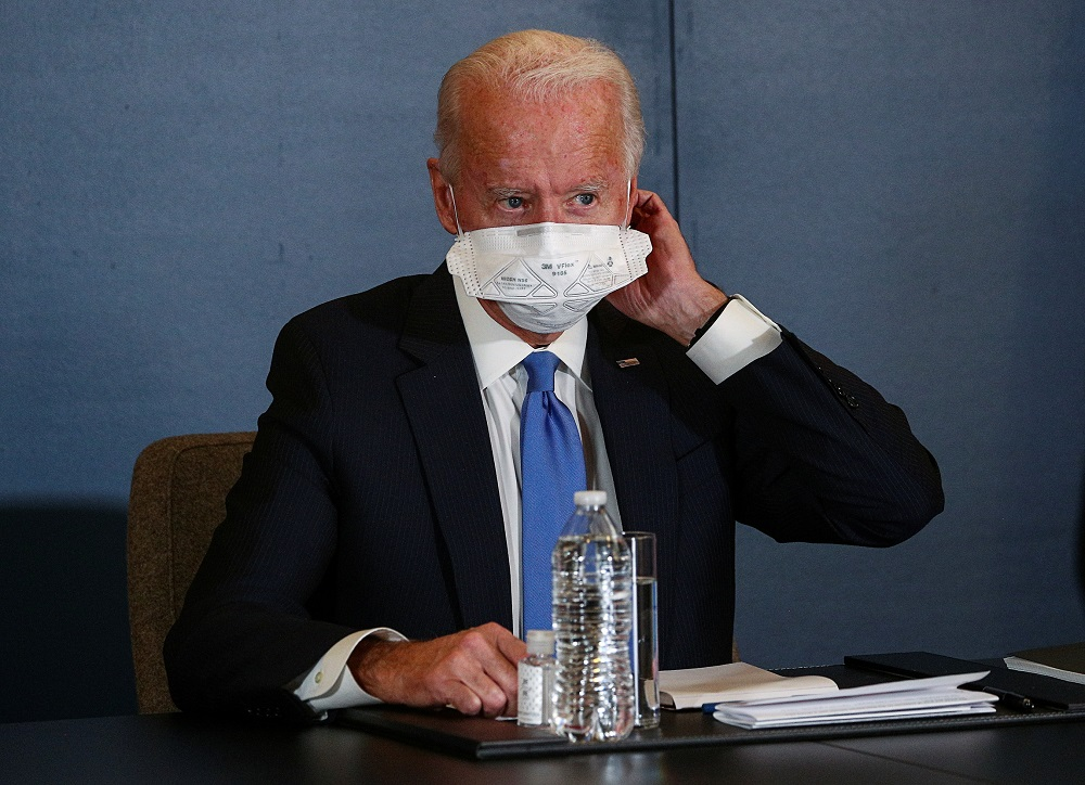 US President-elect Joe Biden removes his face mask as he meets with Speaker of the House Nancy Pelosi and Senate Minority Leader Chuck Schumer at his transition headquarters in the Queen theatre in Wilmingt