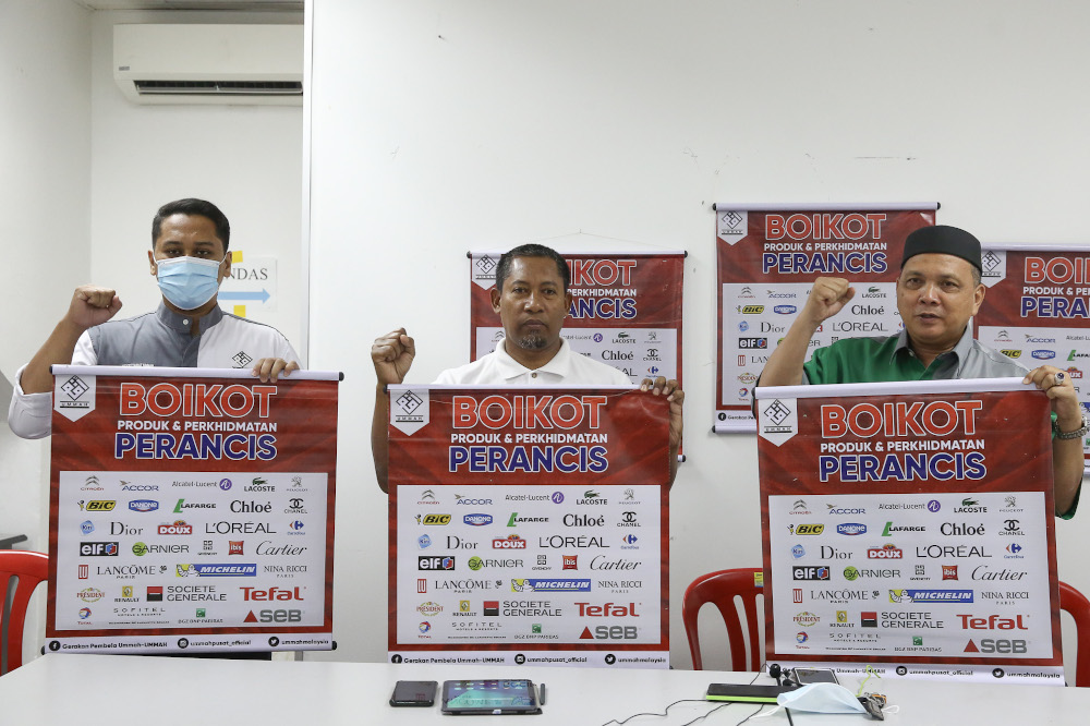 Ummah chairman Mohd Zai Mustafa (centre) poses for a group picture as they hold up placards to boycott French goods and services in Kuala Lumpur November 1, 2020. — Picture by Yusof Mat Isa