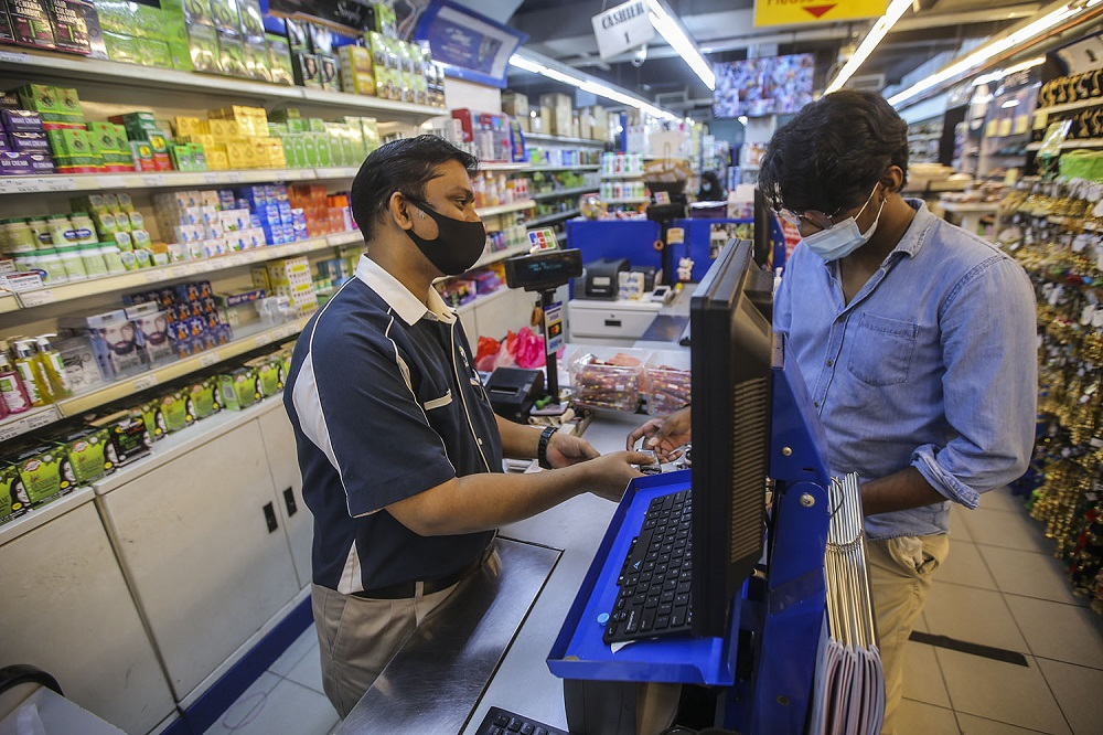 Jahir Hussein (left) attends to customers at his shop in Brickfields, Kuala Lumpur.