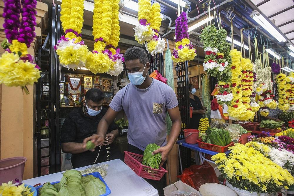 Malai flower traders R. Kuna (right) works at his shop in Brickfields, Kuala Lumpur November 11, 2020.