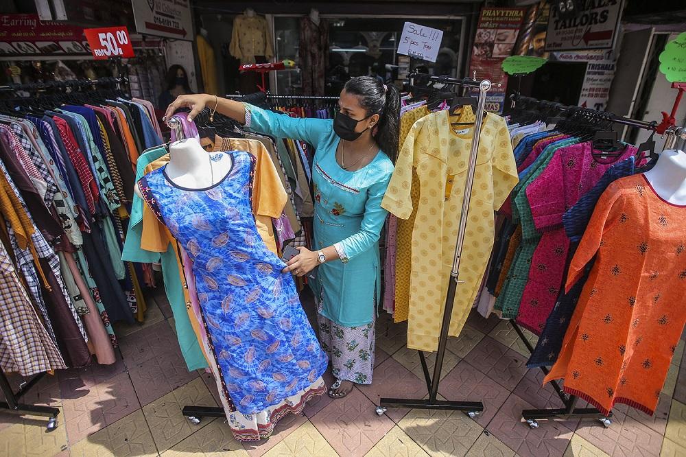 Kogila Prieyaah arranges clothing outside BGV boutique in Brickfields, Kuala Lumpur.
