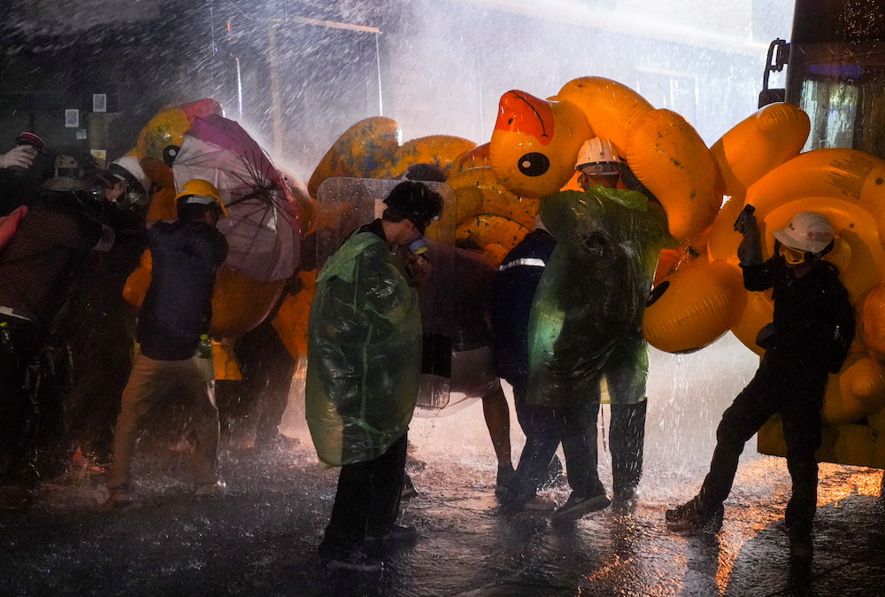 Demonstrators use inflatable rubber ducks as shields to protect themselves from water cannons during an anti-government protest as lawmakers debate on constitution change, outside the parliament in Bangkok, Thailand, November 17, 2020. — Reuters pic