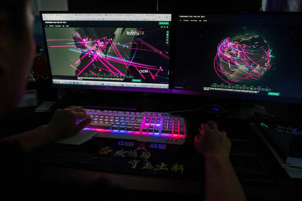Prince, a member of the hacking group Red Hacker Alliance who refused to give his real name, uses a website that monitors global cyberattacks on his computer at their office in Dongguan. — AFP pic