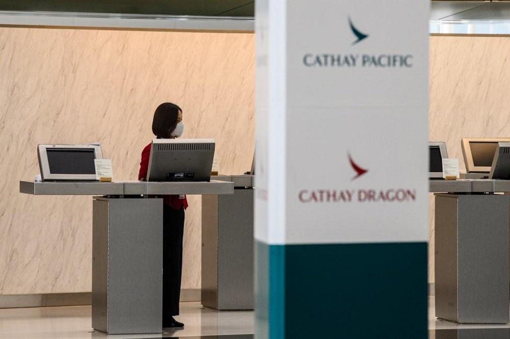 An employee waits for customers at a counter for Cathay Pacific and Cathay Dragon at Hong Kong International Airport October 20, 2020. — AFP pic