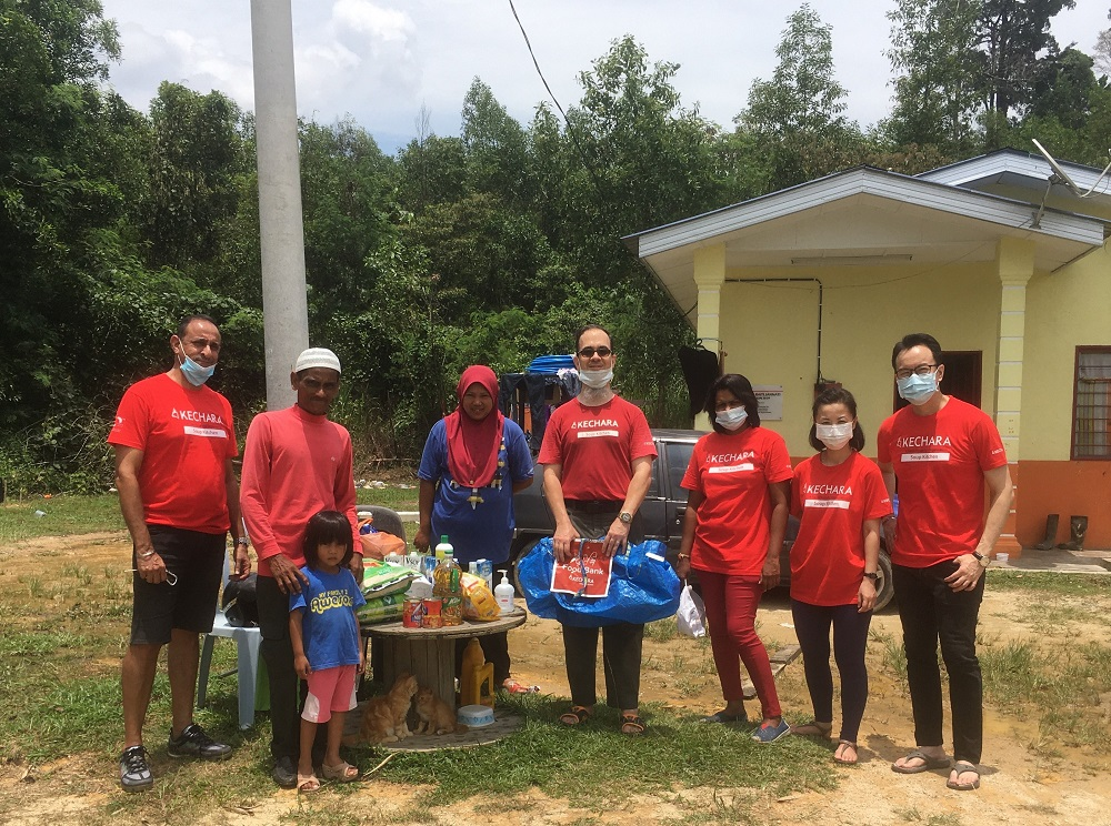 Volunteers of the Negeri Sembilan Kechara Soup Kitchen (in red) after distributing food items to needy communities. — Picture courtesy of Justin Cheah