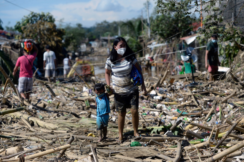 A woman and a child walk on debris brought by the flood following Typhoon Vamco, in Rodriguez, Rizal province, Philippines, November 13, 2020. — Reuters pic