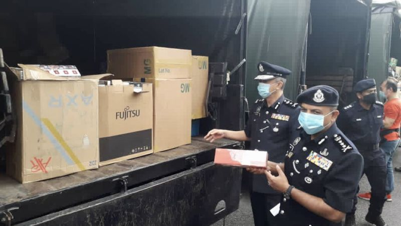 Johor police chief Datuk Ayob Khan Mydin Pitchay (right) with contraband cigarettes that were scheduled to be disposed of by the authorities following the completion of the cases. — Picture by Ben Tan
