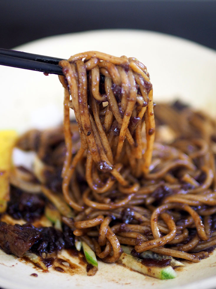 Mix the black bean sauce to thoroughly coat the thick, chewy noodles and slurp it all down
