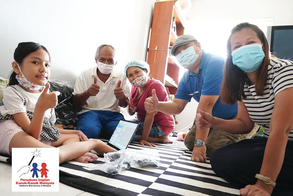 Noralisa Sofia Mohd Azeli (left) and her family members give a thumbs up to the new laptop. — Picture courtesy of Children's Wish Society of Malaysia
