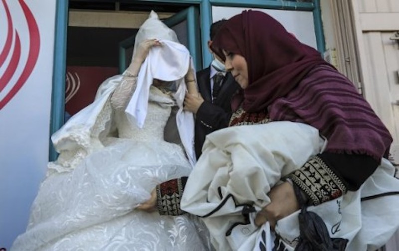 A veiled Palestinian bride covers her face as she leaves a beauty salon in the northern Gaza Strip. — AFP-Relaxnews pic