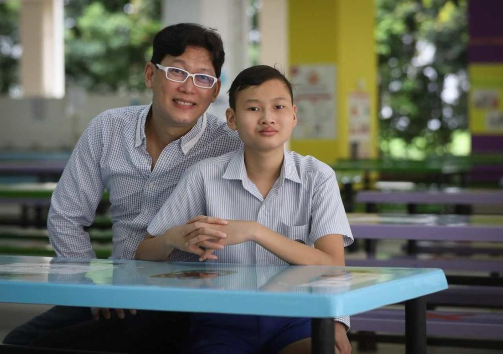 Teh Jun Hang and his father Nicholas Teh. After a long road to recovery, Jun Hang, now aged 13, was one of the 39,995 Primary 6 pupils who collected their Primary School Leaving Examination results on Wednesday. — TODAY pic