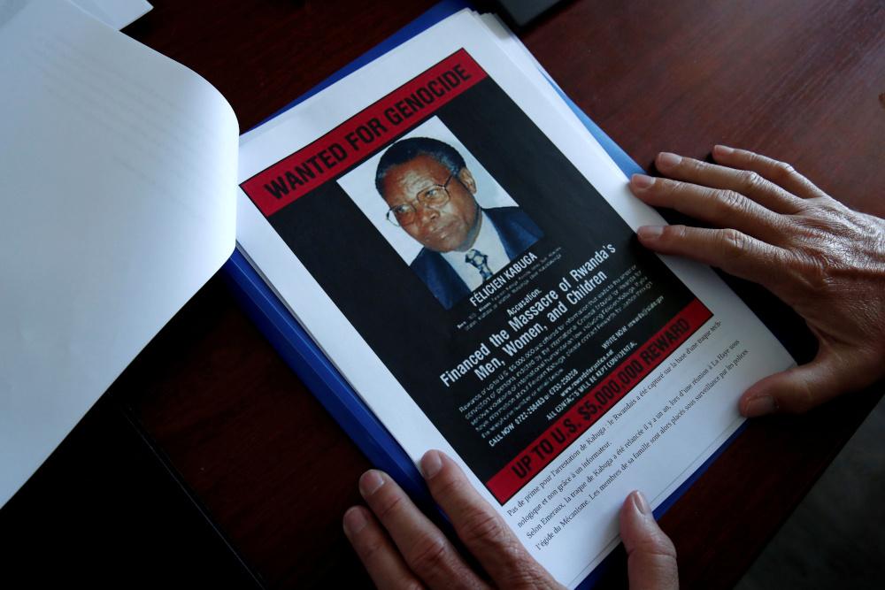 Eric Emeraux, Leiter des Zentralbüros der Gendarmerie zur Bekämpfung von Verbrechen gegen die Menschlichkeit, Völkermorden und Kriegsverbrechen, zeigt Dokumente mit einem Fahndungsplakat, auf dem ein Foto von Felicien Kabuga während eines Interviews mit Reuters in seinem Büro über die Verhaftung des flüchtigen Verdächtigen des Völkermordes in Ruanda, Kabuga, abgebildet ist , in Paris, Frankreich, 19. Mai 2020. - Reuters Bild