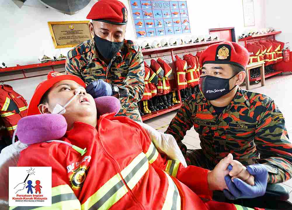 Cancer-stricken Arsyad Ruzin became a firefighter for a day and put out a fire with the help of the firefighters from the Subang Jaya Fire Station. — Picture courtesy of Children's Wish Society of Malaysia