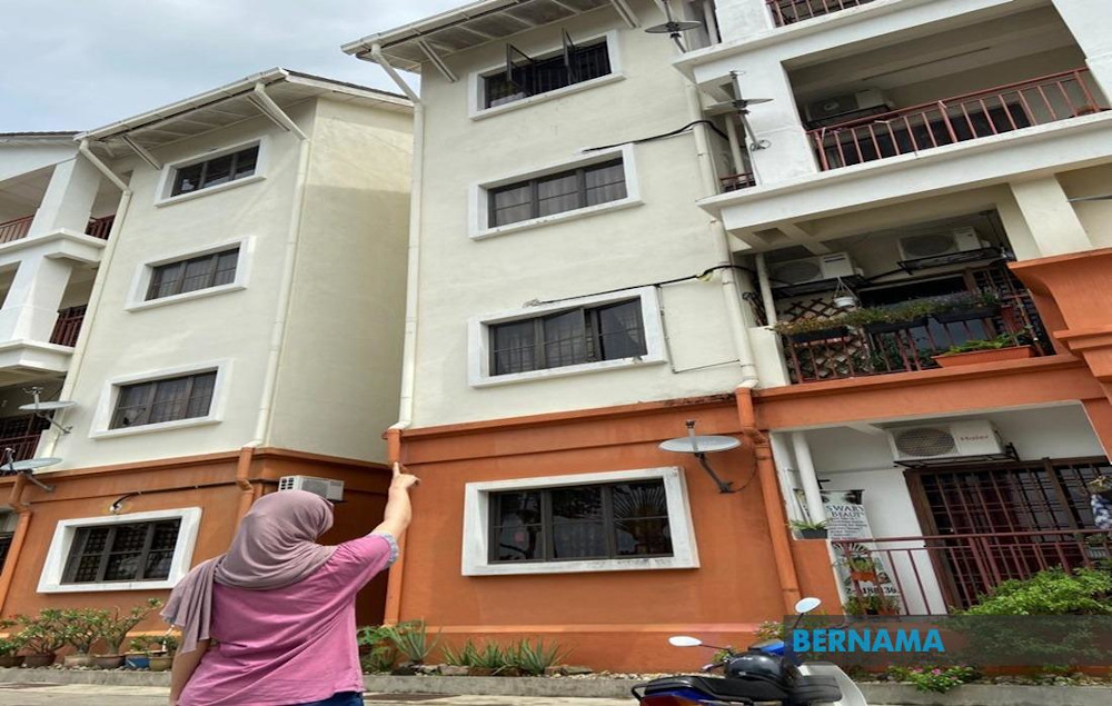 A woman points towards the appartment where a man was arrested for allegedly throwing his four-year-old step-grandson out of a window in Danau Kota, Setapak November 29, 2020. — Picture via Twitter/Bernama