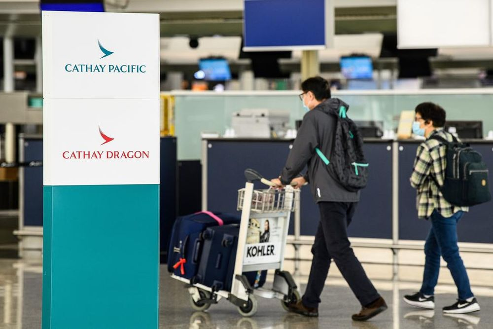 Passengers walking near Cathay Pacific check-in counters at Hong Kong International Airport on Oct 20, 2020. — AFP pic