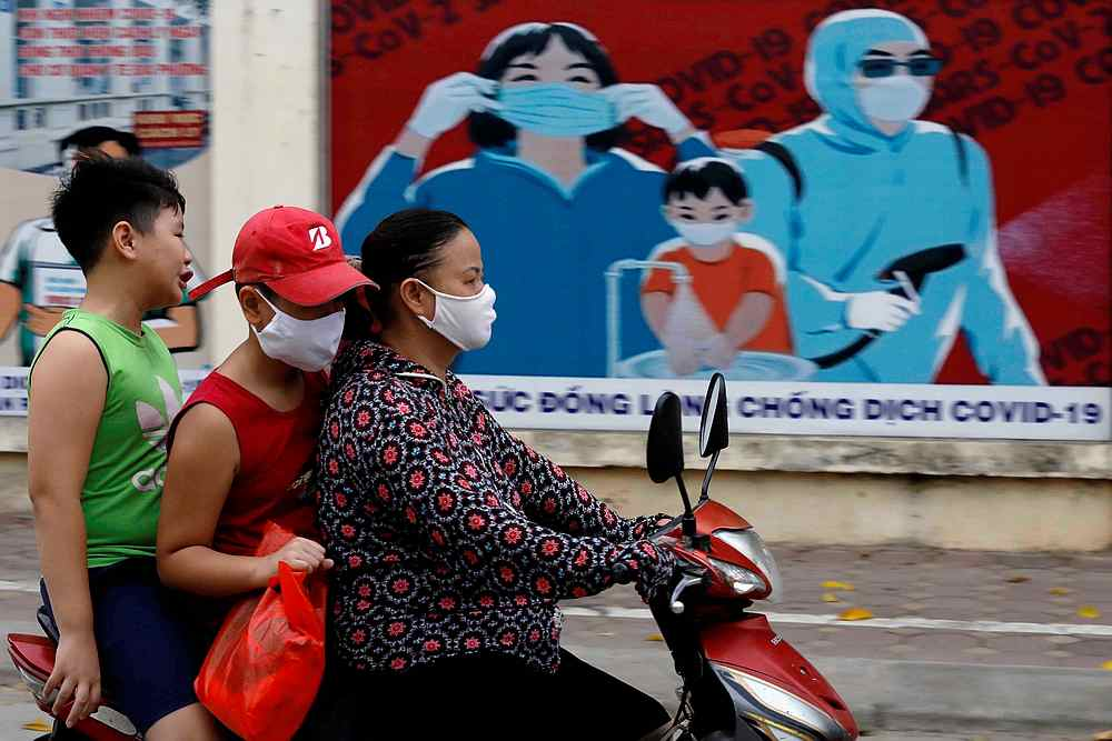 A woman wears a protective mask as she drives past a banner promoting prevention against Covid-19 in Hanoi, Vietnam July 31, 2020. — Reuters pic