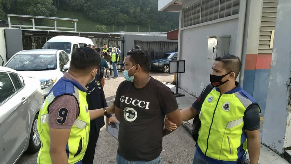 Accused Dinesh Kumar (centre) being escorted by policemen before he was charged with six counts of rape, sodomy, extortion and injuring a woman in Johor Baru today. — Picture by Ben Tan