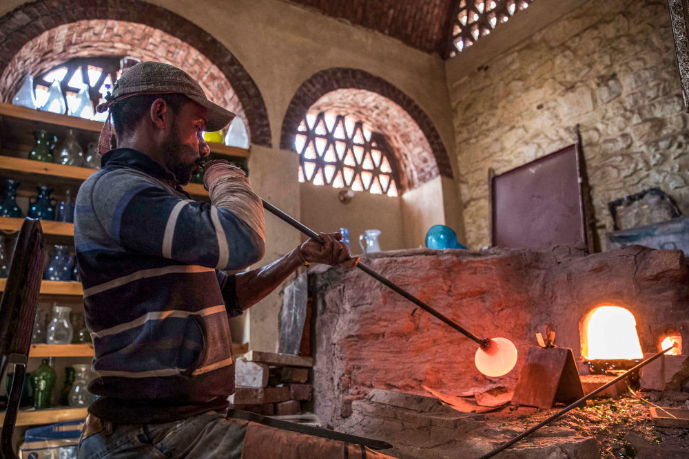 A glassblower sculpts a vessel at a workshop near the 15th century Sultan Qaitbay mosque complex in the City of the Dead area of Egypt's capital Cairo November 1, 2020. — AFP pic