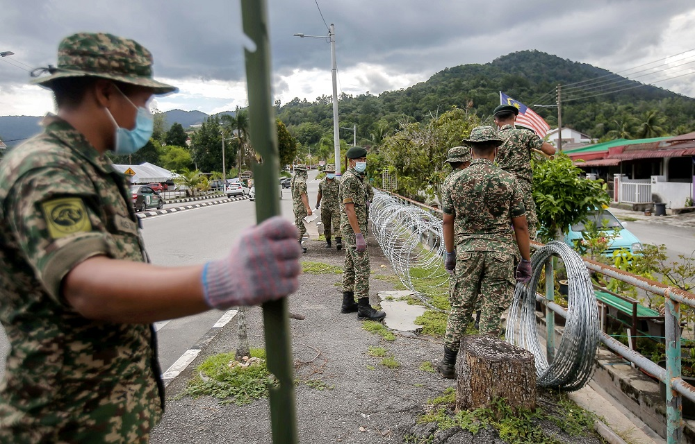 Armed Forces personnel are seen putting up barbed wires at Zon B and Zon C of Taman Meru 2C in Ipoh that will be put under the enhanced movement control order (EMCO) for two weeks. ― Picture by Farhan Najib
