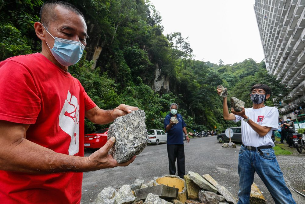 Socialist Progressive Front Party Central Committee member Teh Yee Cheu (left) holds up a piece of boulder debris found along Grandview Heights, Paya Terubong November 2, 2020.