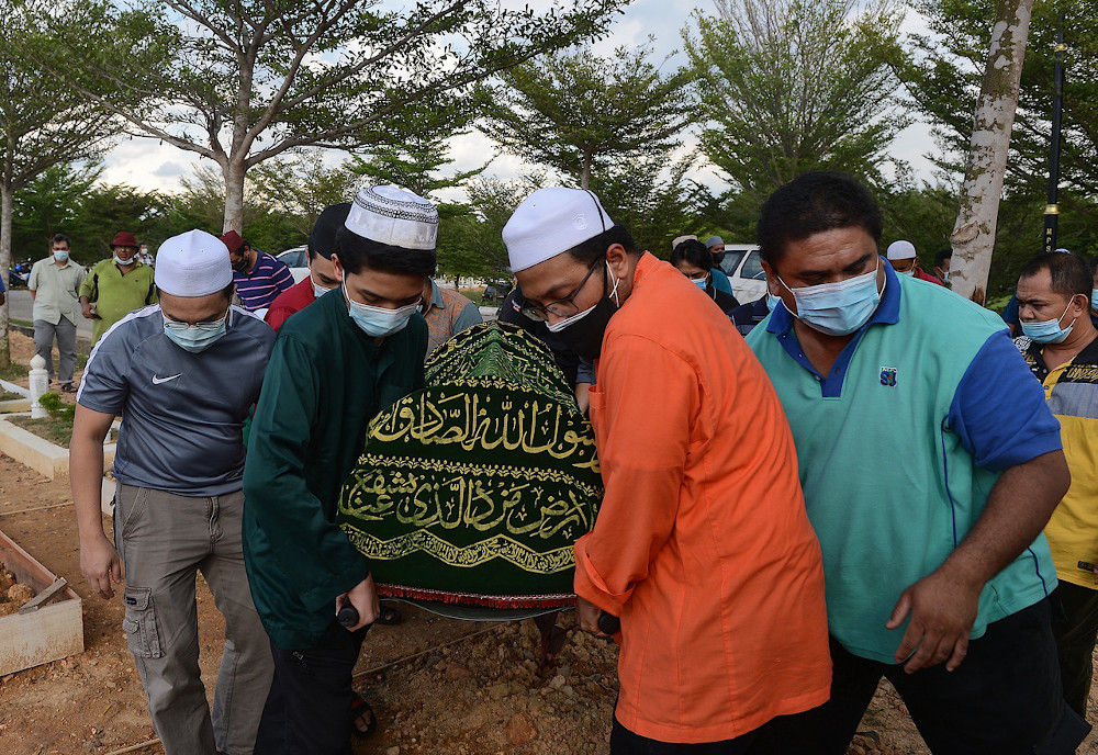 Farhan Hasif (2nd left) carries the body of his father Mohd Irfan Fikri Mohd Rawi at the Subang USJ22 Muslim cemetery, November 9, 2020. — Bernama pic