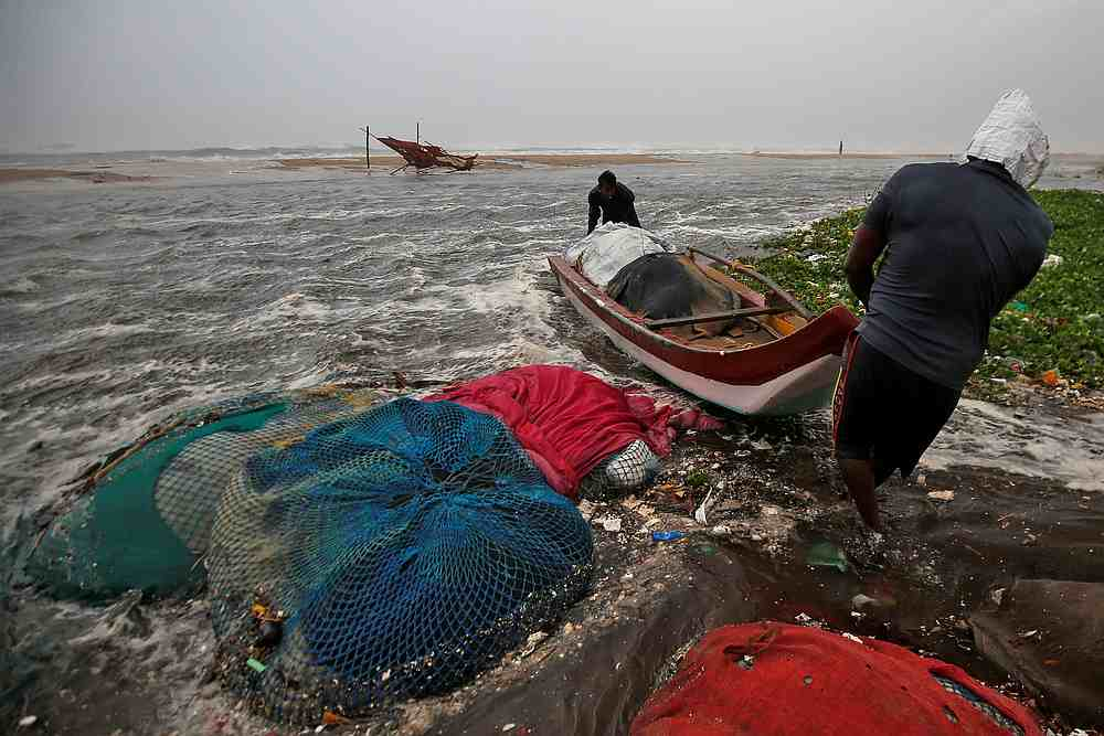 Fishermen move a fishing boat to a safer place along the shore before Cyclone Nivar's landfall, in Chennai, India November 25, 2020. — Reuters pic