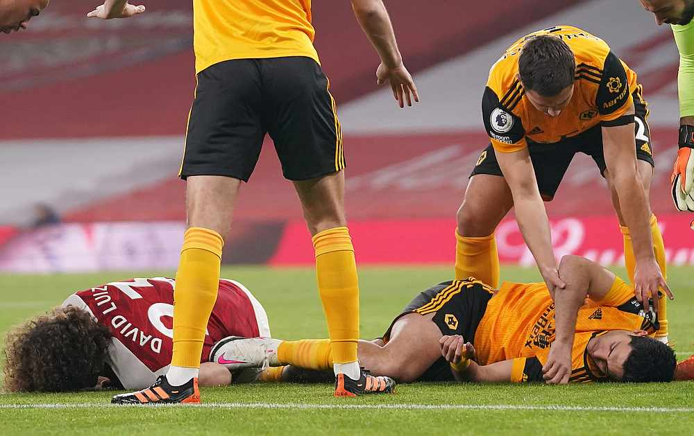 Arsenal's David Luiz and Wolverhampton Wanderers' Raul Jimenez (on the ground, right) after a head-on collision during their EPL match at Emirates Stadium, London November 29, 2020. — Pool pic via Reuters
