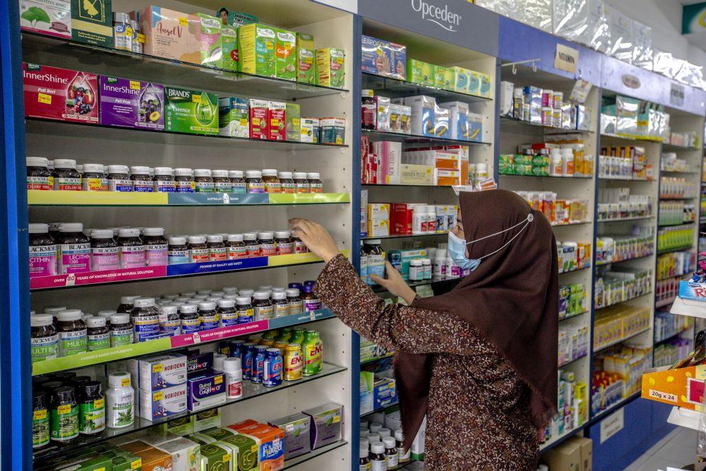 A pharmacist arranges bottles of medicine at a pharmacy in Kampung Baru, Kuala Lumpur November 5, 2020. — Picture by Firdaus Latif